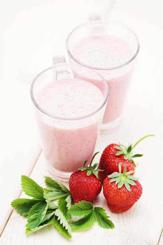 Clean Eating Strawberry Smoothie in two, clear, glass mugs with fresh strawberries laying next to them on a white table.