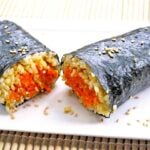 One of these Nori Carrot Wraps sit on a white plate, cut in half so you can see the bright orange carrots inside.