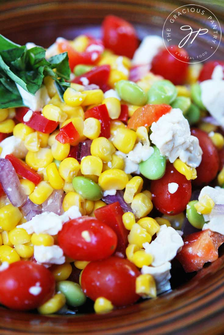 A close up shot of this Clean Eating Corn Salad showing all the bits of corn, feta and fresh basil as well as tomatoes.