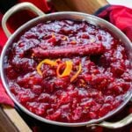 This Homemade Cranberry Sauce is being served in a bowl. Looking from the top down, you can see all the cooked, bright red cranberries, the cinnamon stick and the orange peel garnish. It's ready to eat!