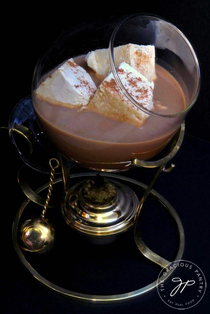 A brandy warmer sits filled with hot chocolate and three square marshmallows.