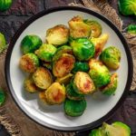 A single plate sits on a dark, brick background. It holds a beautiful pile of roasted, golden-brown brussels sprouts which have been cut in half.