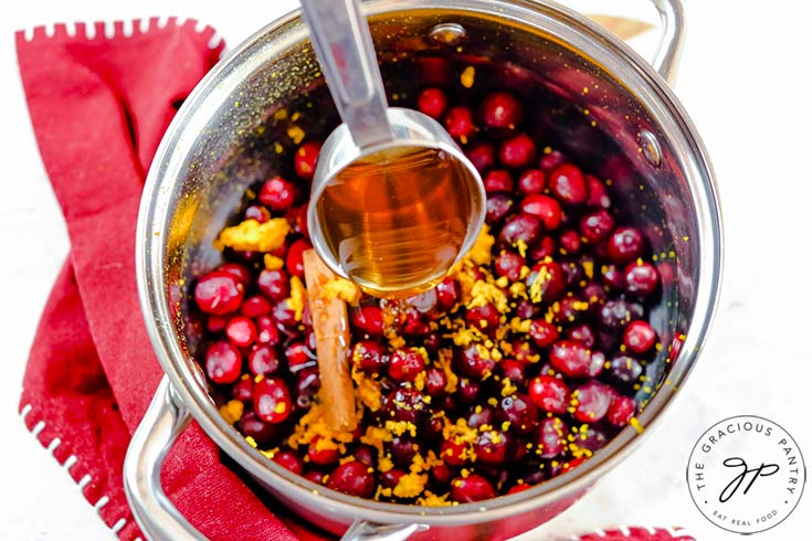 Step four of this Homemade Cranberry Sauce is to add the honey.