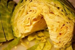 A cut cabbage that has been cored and is ready for slicing