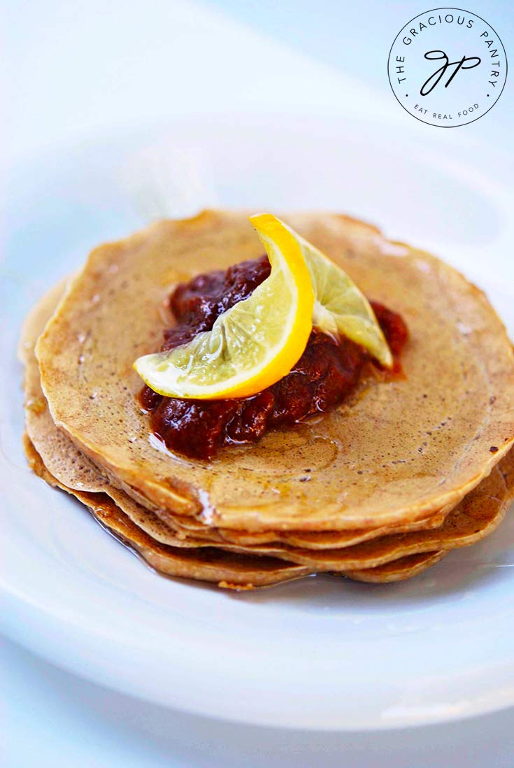 A delicious looking stack of Whole Wheat Pancakes topped with fruit compote and a lemon slice.