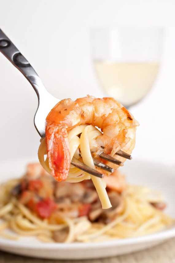 In this image, the camera focuses on a fork being held with a small bit of pasts wrapped around it and a large shrimp. In the background, you see a bowl of Clean Eating Shrimp Scampi and a glass of white wine.