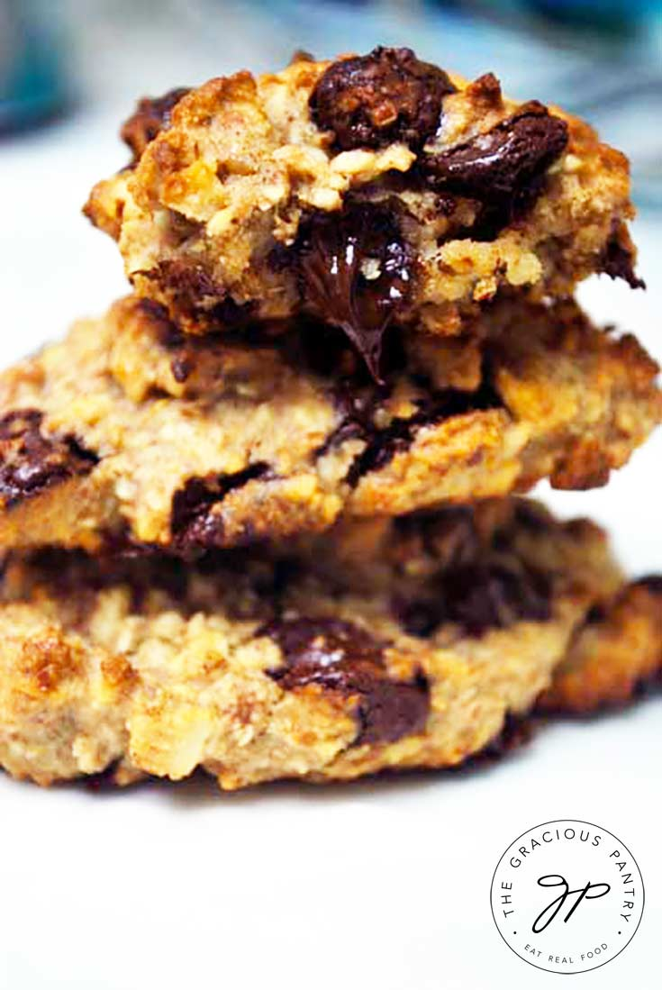 A stack of 3 Clean Eating Chocolate Chip Cookies with a bite taken out of the one on top. The warm chocolate chip that was bitten is oozing down out of the cookie.