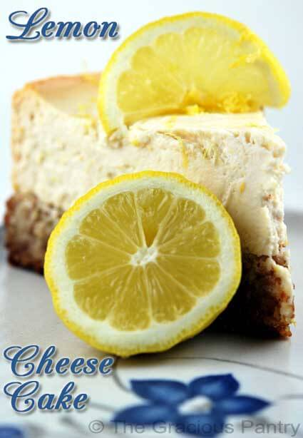 A slice of lemon cheese cake with a slice of lemon on top and a half a lemon sitting next to the slice on a white cake.
