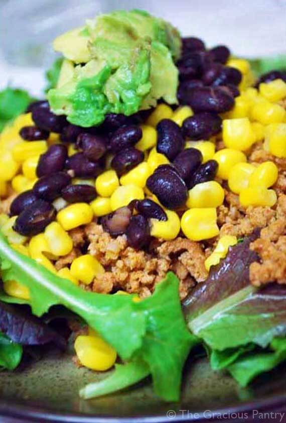 An up close image of this Clean Eating Taco Salad showing meat, corn, black beans and topped with avocado.
