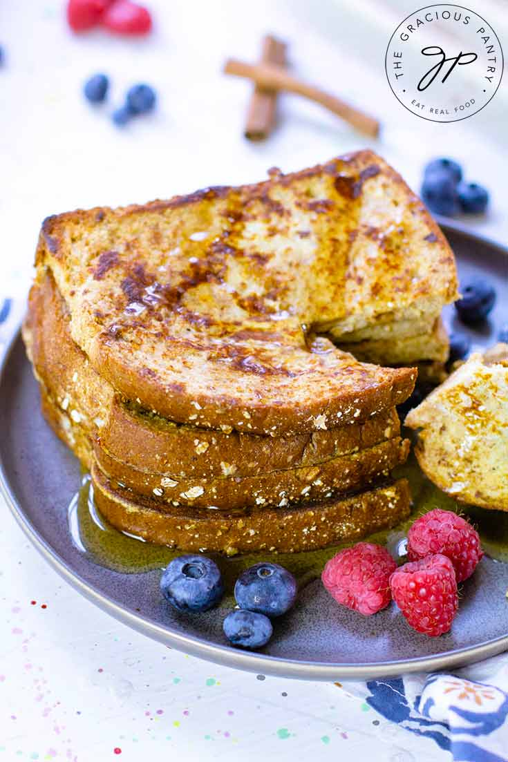 A stack of Healthy French Toast sits on a plate with fresh raspberries and blueberries. The toast is stacked and has a piece cut out of it.