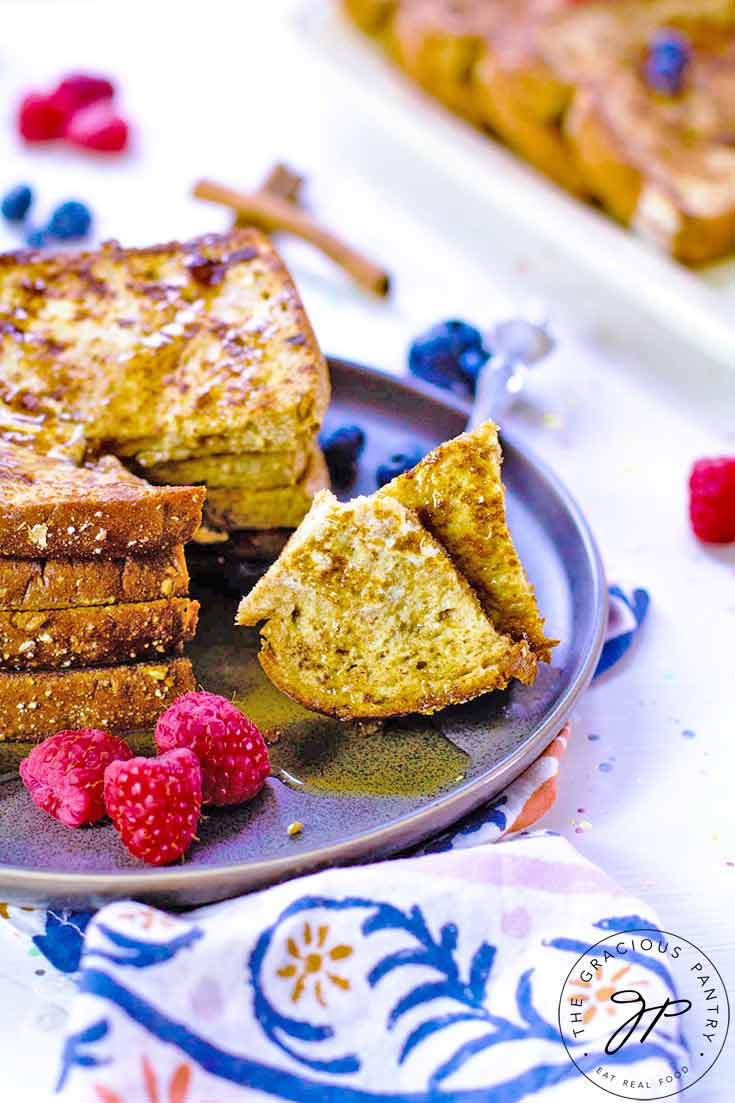 A slice of the stack of french toast sitting on a plate has been cut and rests on a fork on a plate next to the stack of french toast.