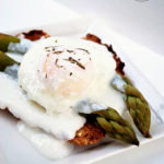 A slice of toast sits topped with two asparagus spears, a poached egg, and has white sauce drizzled over the top in this Clean Eating Easy Eggs Benedict Recipe.