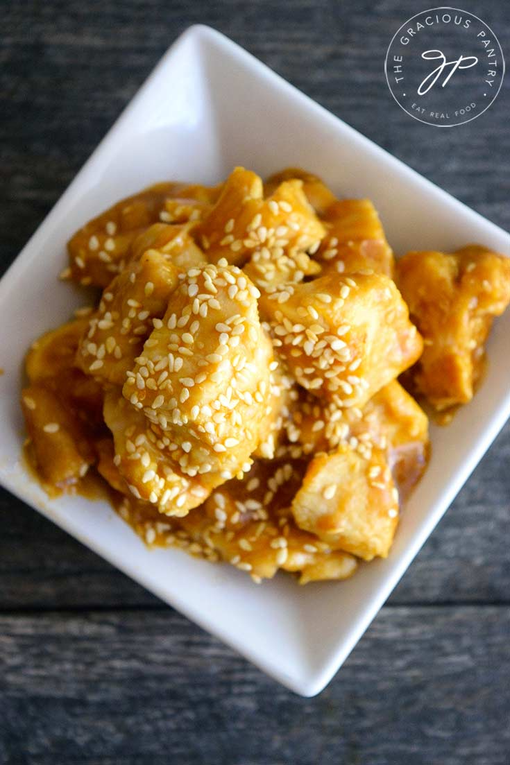An overhead view looking down into a square, white bowl of this sesame chicken recipe. Sesame seeds are predominantly garnishing the chicken with lots of glaze.