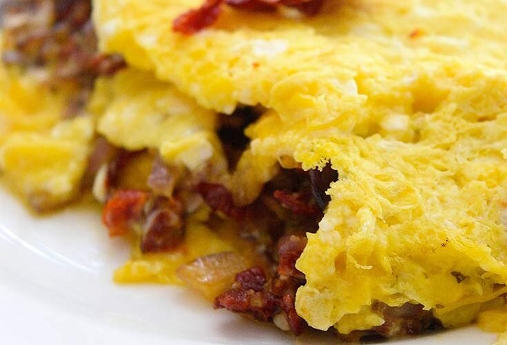 A delicious, Sun Dried Tomato Omelet sits served on a white plate, ready to eat.
