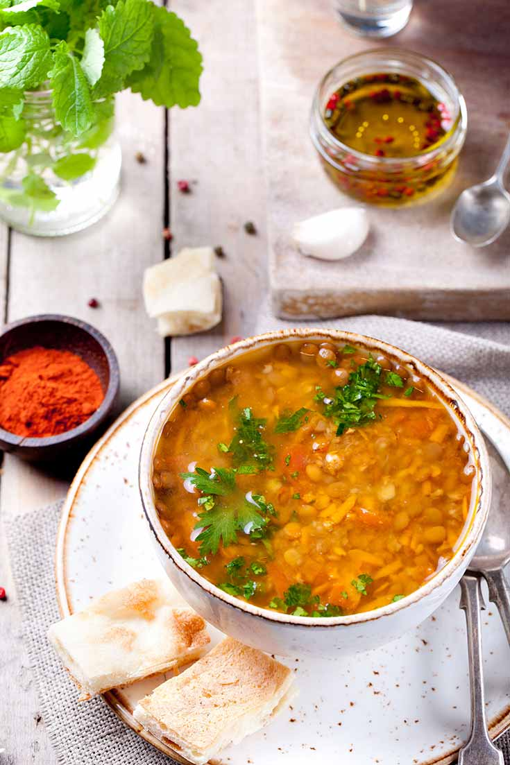 A bowl of this clean eating german lentil soup recipe sits on a white plate with some crackers on the side.