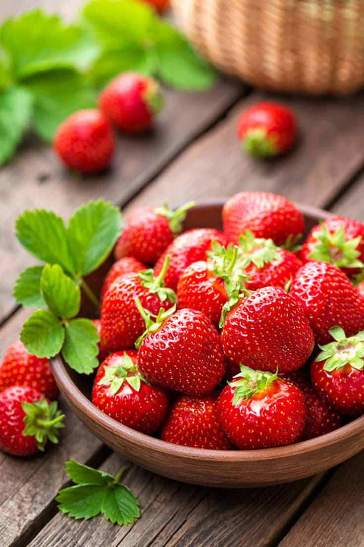 Strawberries in a wooden bowl depicting this list of clean eating 300 calorie snacks