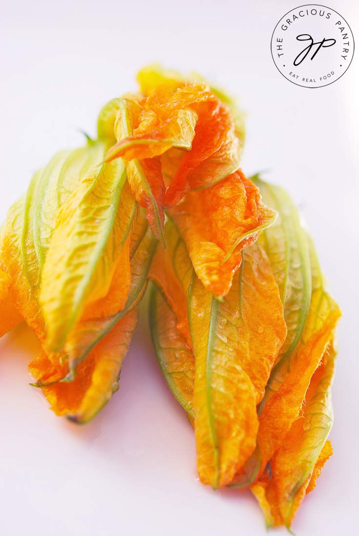 Three raw squash blossoms sit ready to be cooked with this Squash Blossoms Recipe.