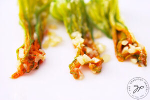 A row of three, cooked squash blossoms.