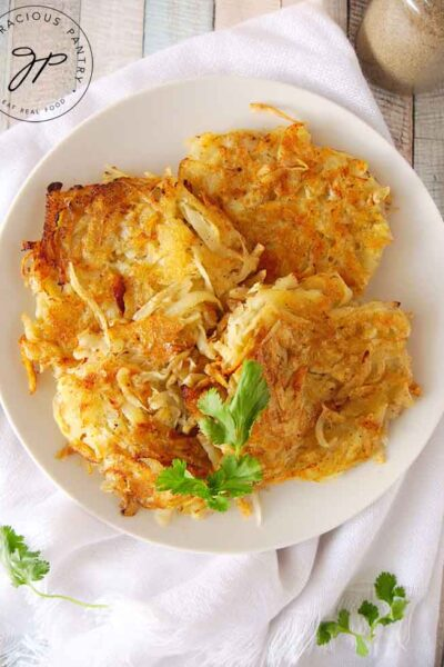 This Homemade Hash Browns Recipe has been served on a white platter. A big stack of golden brown hash browns sits on a white plate, ready to eat.