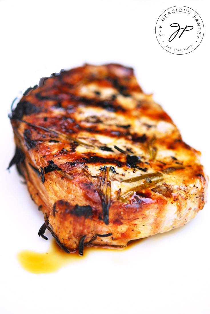 A single chops from this Clean Eating barbecue Rosemary Pork Chops recipe sits on a white background. It's beautifully caramelized with a tiny bit of the juices on the white plate.