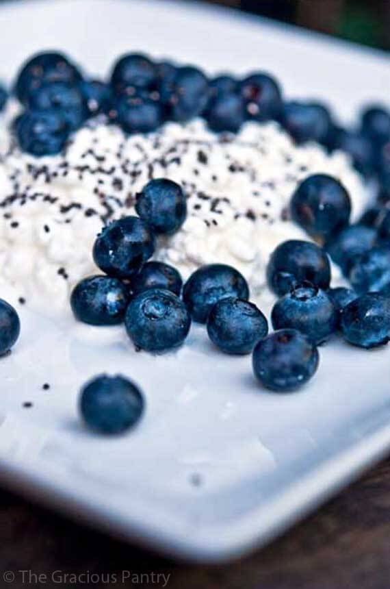 A close up shot of this Clean Eating Blueberry Cottage Cheese shows a square, white plate holding a layer of cottage cheese with blueberries and chia seeds sprinkled over the top.