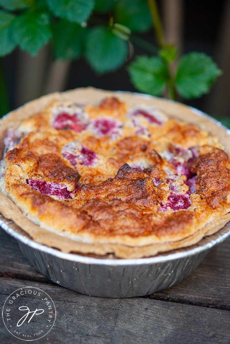 A just-baked Raspberry Pie sits on an outdoor bench, cooling. Green foliage sits behind it.