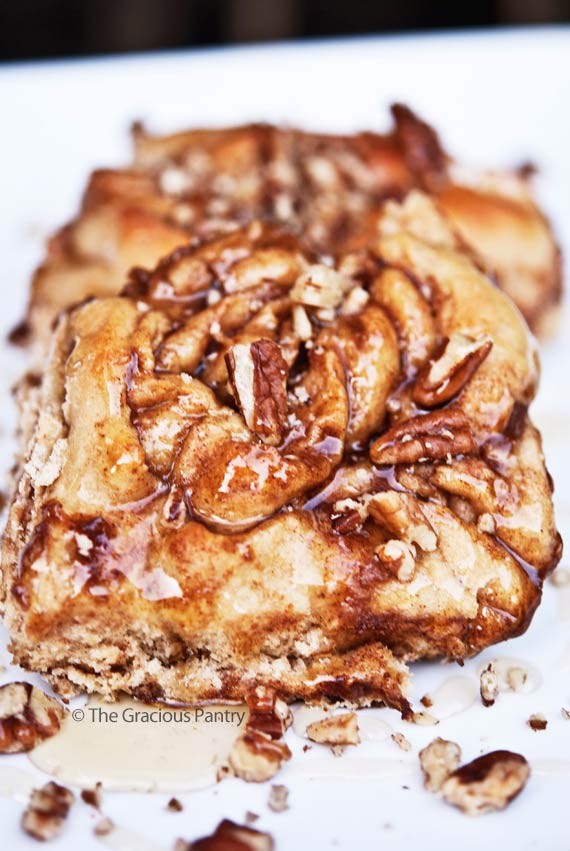 Clean Eating Cinnamon Rolls shown up close on a white platter. You can see the glaze of honey over the buns and pieces of pecans are sprinkled over the top.