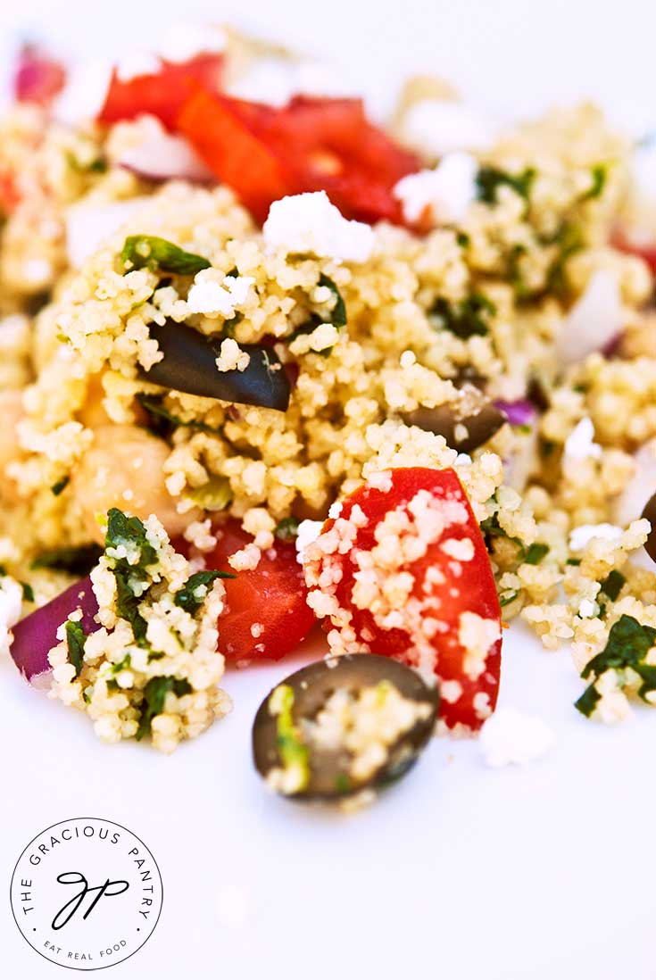 A large helping of this clean eating Greek couscous salad falls over the entirety of a white plate. You can see chunks of tomatoes, olives and feta cheese.