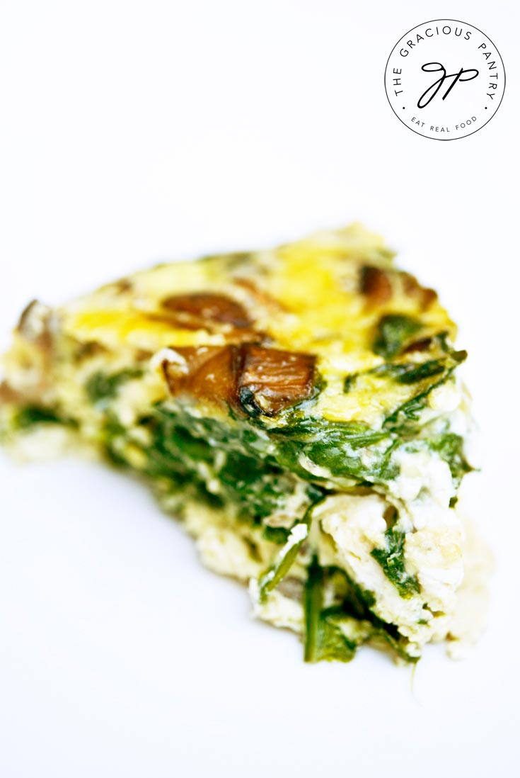 A close up shot of a single slice of this Clean Eating Garlic Mushroom And Spinach Frittata. You can see the mushrooms and spinach cooked in throughout the piece of frittata.