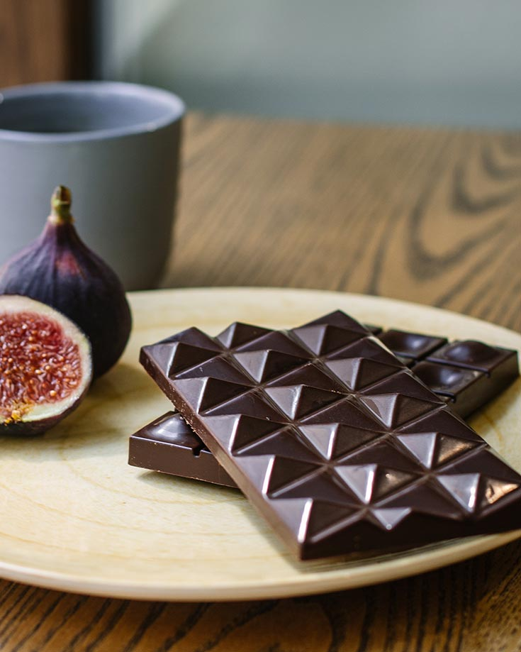 A bar of chocolate sits on a cutting board next to a cup and fig in this article that discusses, Is Chocolate Good For You?