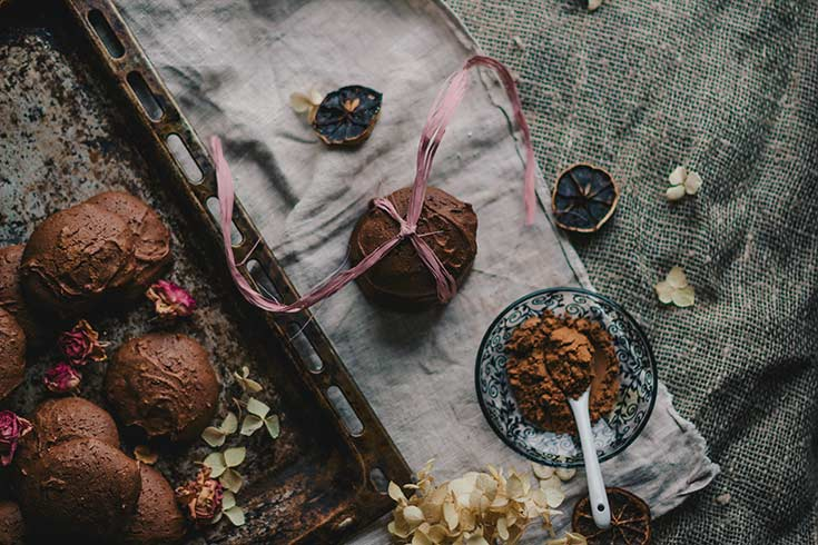 An overhead view of a bowl of cocoa powder next to a stack of chocolate cookies.