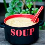A black and red bowl sits filled with this Sick Day Soup Recipe