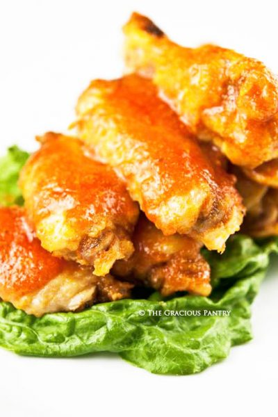 A big stack of these Baked Chicken Wings sit on a bed of green lettuce with an orange-colored, spice sauce drizzled over the top.