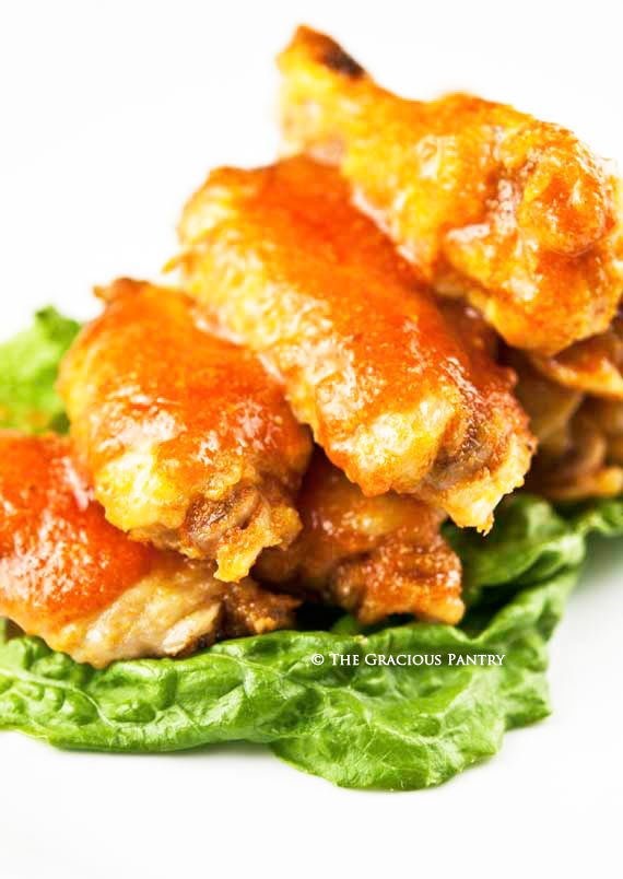 Clean Eating Spicy Buffalo Wings piled high on a bed of green lettuce and on a white serving platter. the red-orange buffalo sauce is nicely roasted onto the wings.