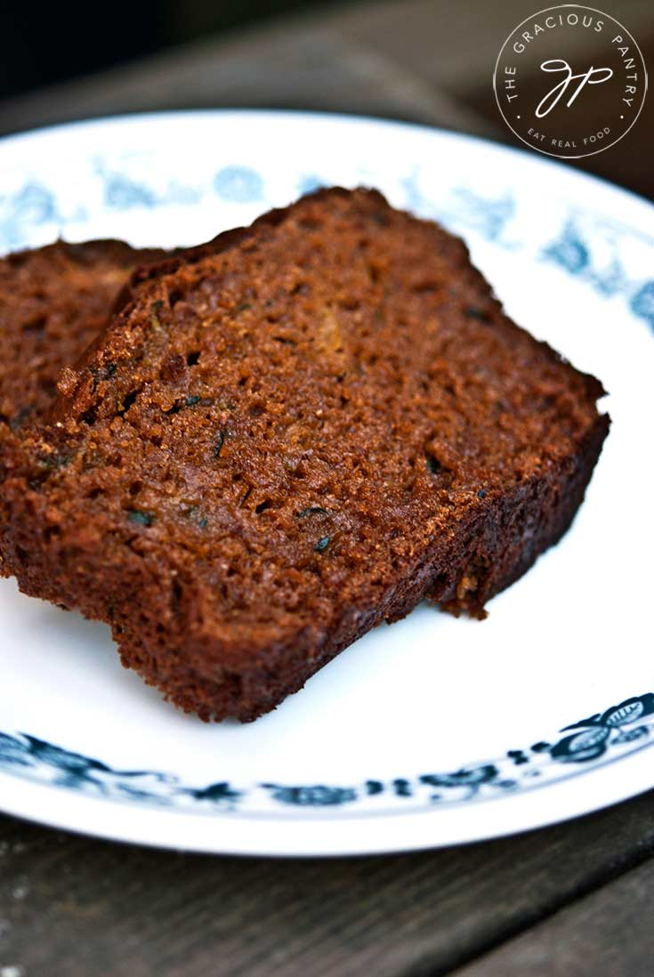 Two slices of dark brown, Clean Eating Zucchini Bread sit on a white plate, ready to serve.