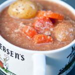 A soup bowl with a mug handle sits filled with this Pork Stew Recipe