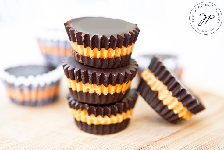 A head on view of a stack of 3 clean Eating Peanut Butter Cups stacked up with a few other single peanut butter cups scattered around the stack.