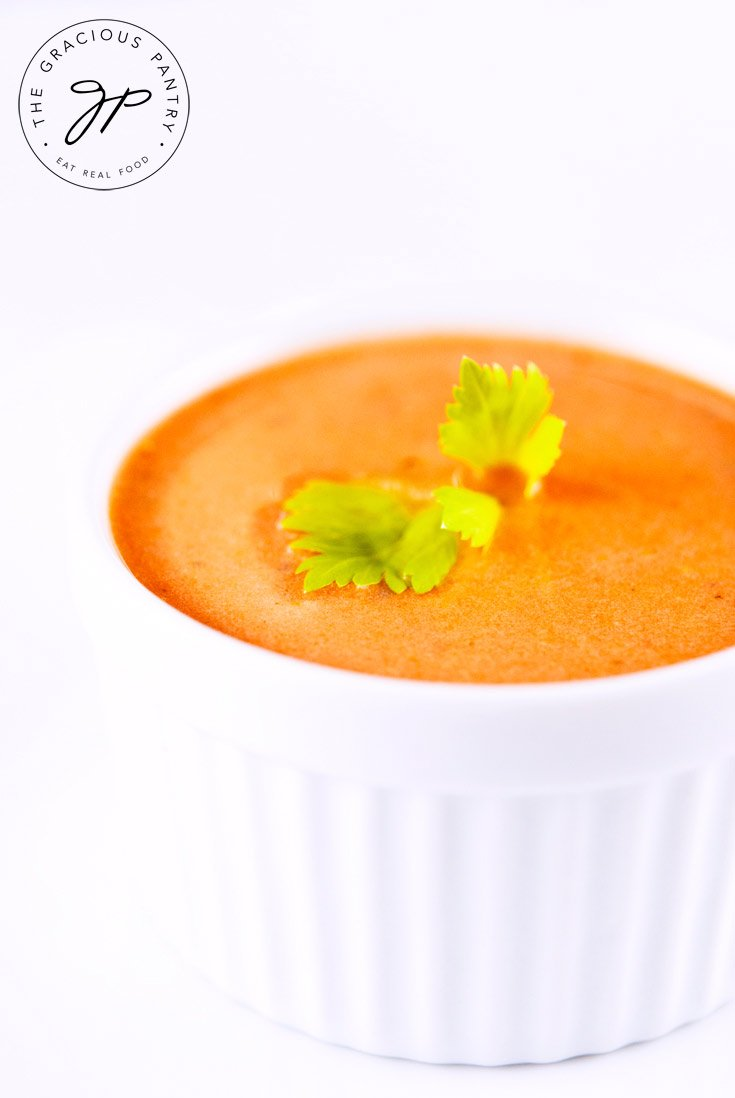 A white bowl on a white background brings out the orange red in this Clean Eating Tomato Soup. There is a small sprig of bright green celery leaf sitting on top of the soup at the center.