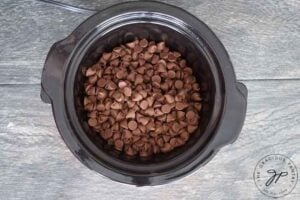 Pour chocolate chips into slow cooker.