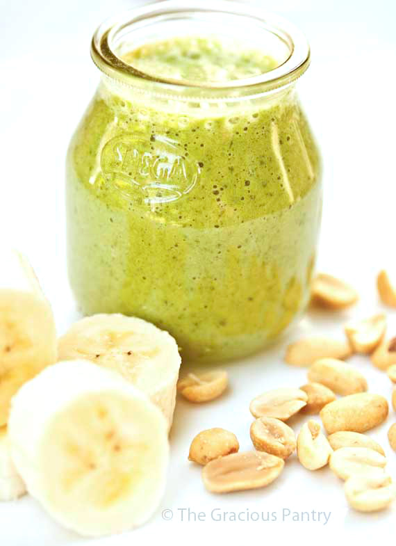 A small, clear, bless jar filled with this green, Clean Eating Peanut Butter And Banana Smoothie sits on a white background amidst sliced bananas and peanuts.