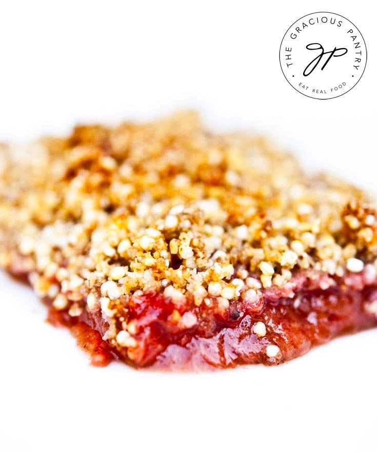 A slice of this Clean Eating Strawberry Rhubarb Apple Crisp sits on a completely white background. The crisp on top is a beautiful golden color while the rhubarb layer below is a beautiful, bright pink.