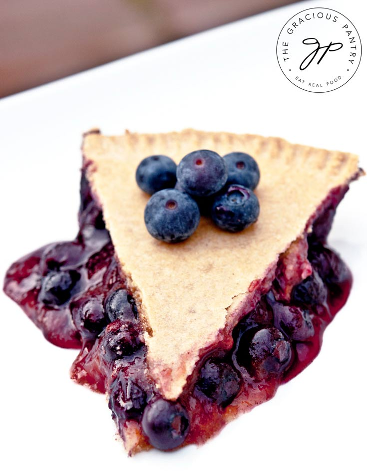 a single slice of Clean Eating Blueberry Pie sits on a white plate, ready to eat. You can see the blueberries on the sides, coming out from under the crust, and a few fresh blueberries sit on top of the slice as well.