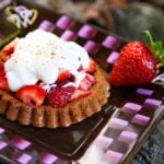 A plate holds a delicious looking strawberry shortcake. It has a golden brown base, a large pile of fresh, sweet strawberries and a dollop of whopped cream, all topped off with a sprinkle of cinnamon.