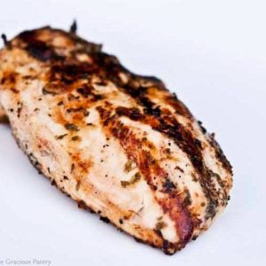 A grilled tarragon chicken breast sits on a white plate, ready to eat.