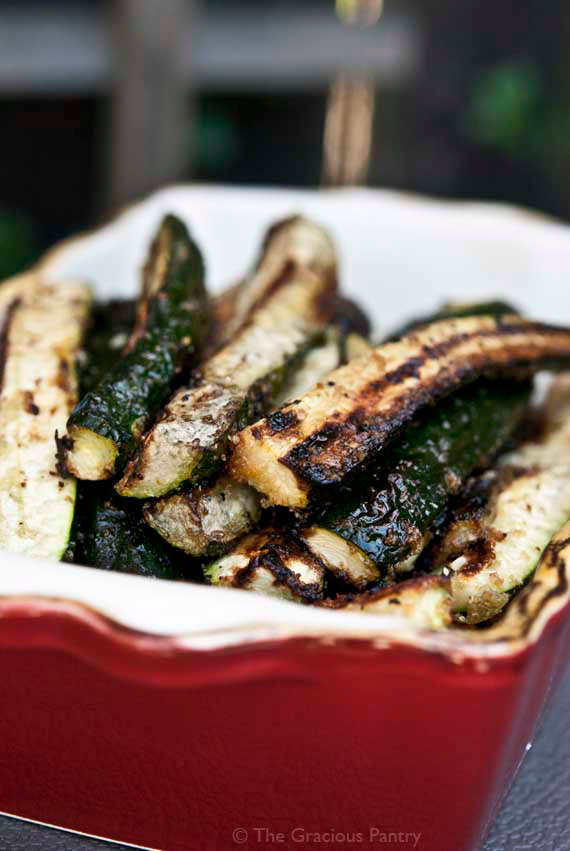 grilled zucchini in red serving dish