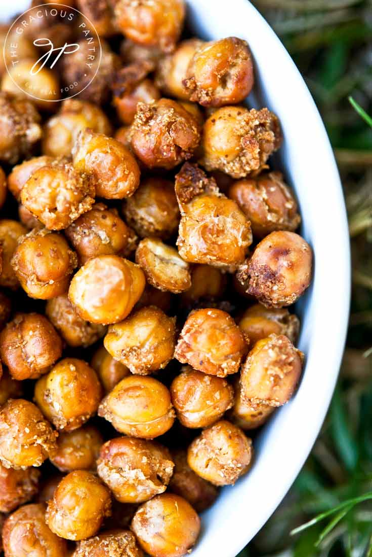 Clean Eating Roasted Chickpeas served in a white bowl and sitting on a green grassy background. Chickpeas are roasted to a rich, golden brown.