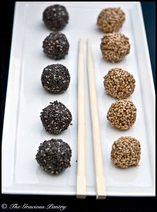 A long, white, rectangular plat with chop sticks laying down the middle carries two rows of Clean Eating Jum Jills. The row on the right has Jum Jills covered in sesame seeds. The row on the left has Jum Jills covered in chia seeds.