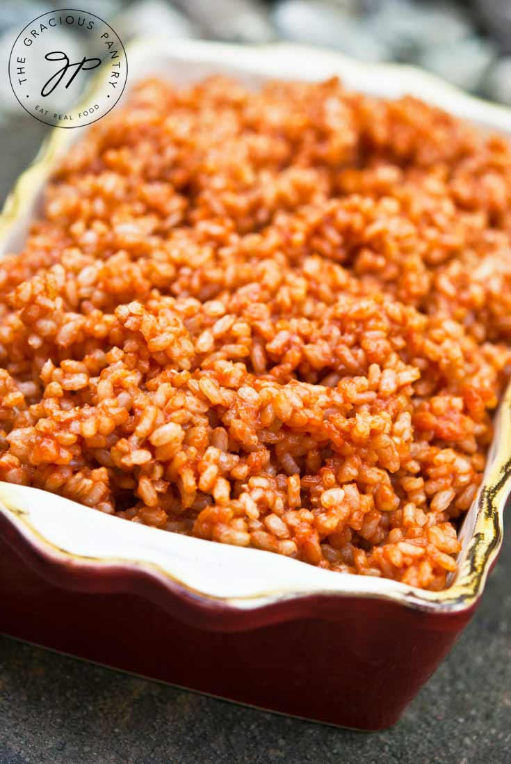 A small, dark red casserole dish is filled with Clean Eating Spanish Rice which is shown up close.
