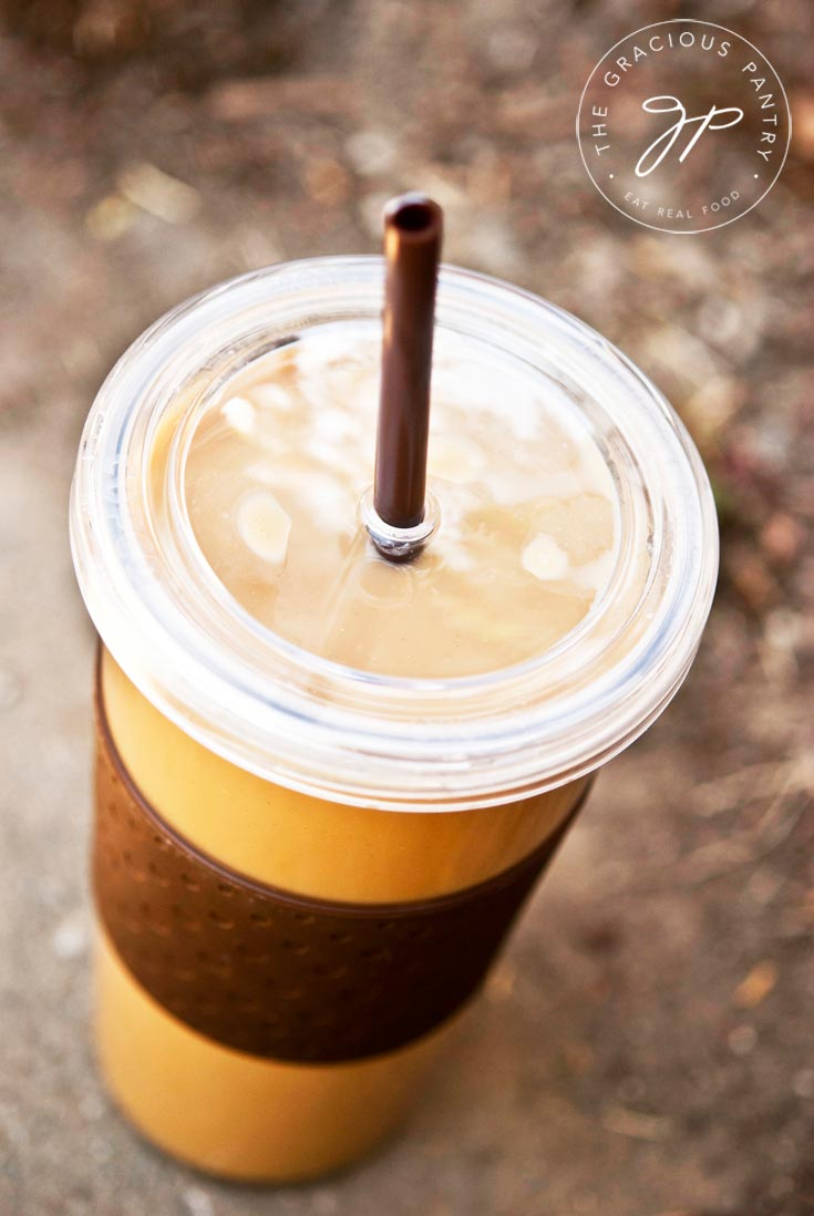 A single, clear cup with a lid and straw filled with this Clean Eating Pumpkin Spice Latte. It looks delicious and ready to drink!