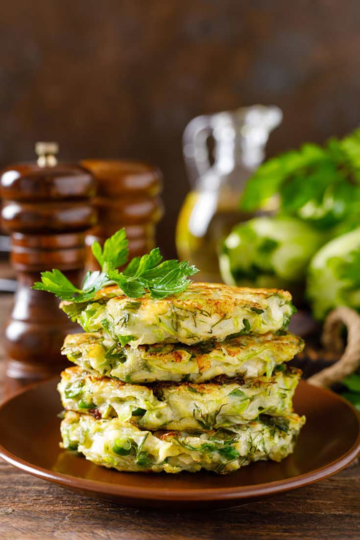 A stack of zucchini fritters sit on a wooden plate. There is an oil bottle and salt and pepper shaker sitting behind the plate. Fresh herbs top the fritters.
